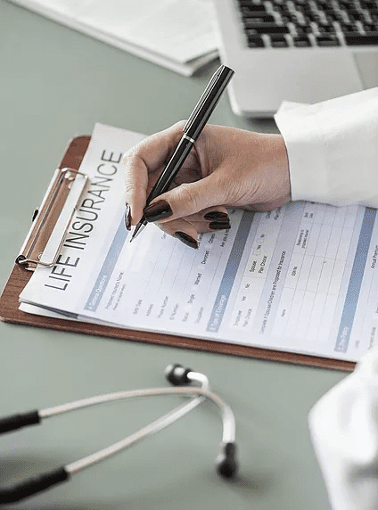 A doctor filing paperwork for life insurance plans