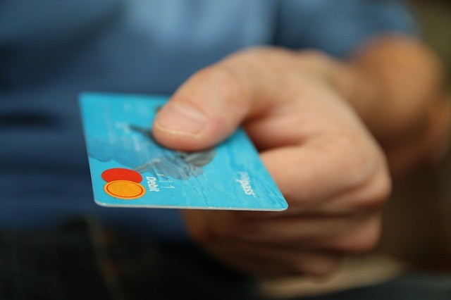 Man with credit card in hand using for pharmacy