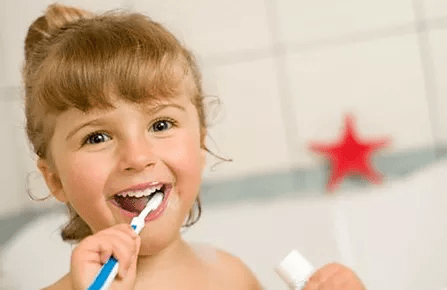 A small child brushing their teeth